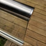 Slotted end cap on slotted handrail installed ontop a glass balustrade on decking