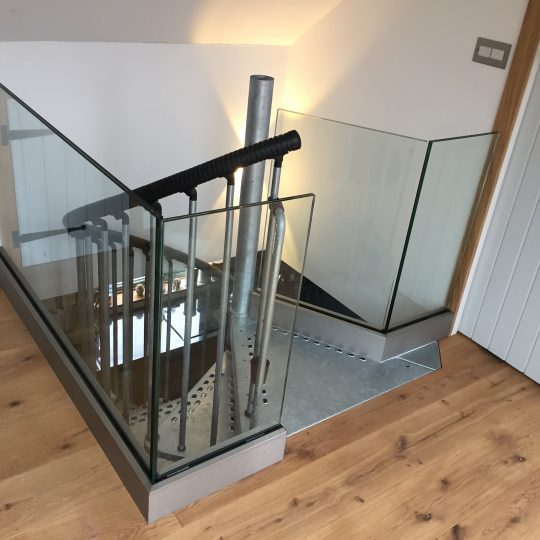 frameless glass balustrade around an opening around the landing