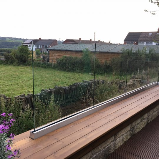 glass balustrade installed on a garden wall