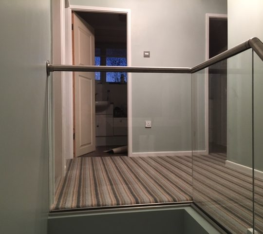 glass balustrade with handrail on a landing and stairs